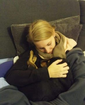 A woman cuddling with her dogs.